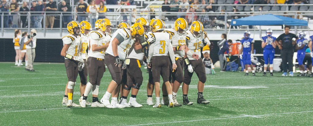 High School Varsity Football Team huddles together